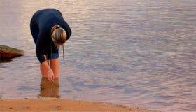 Menina loura que pegara shell de uma lagoa Fotos de Stock Royalty Free