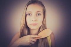 Menina loura que penteia seu cabelo, efeito da grão foto de stock