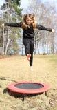Menina loura que salta no trampolim foto de stock