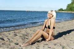 Menina loura que senta-se no mar do azul da costa foto de stock royalty free