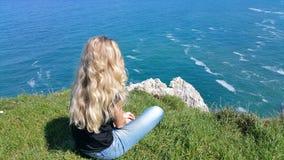Menina loura que senta-se para trás na rocha foto de stock royalty free