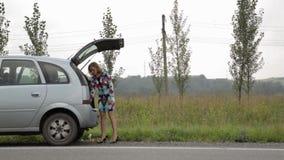 Menina loura que stending perto de seu carro quebrado com o tronco aberto em uma estrada secundária e lido a instrução video estoque