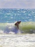 Menina loura que surfa as ondas Fotografia de Stock
