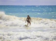 Menina loura que surfa as ondas Fotografia de Stock Royalty Free