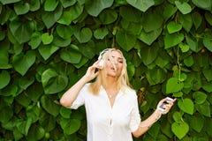 Menina loura que tem o divertimento em um fundo das folhas verdes Foto de Stock Royalty Free