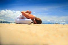 a menina loura senta-se na curvatura dianteira dos lótus do asana da ioga na praia Foto de Stock Royalty Free