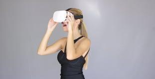 A menina loura 'sexy' bonita aprecia vidros da realidade virtual fotos de stock