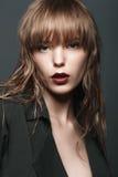 Menina loura 'sexy' com bordos e ouro vermelhos nos olhos em um revestimento escuro Imagem de Stock