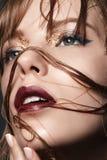 Menina loura 'sexy' com bordos e ouro vermelhos nos olhos em um revestimento escuro Imagens de Stock