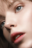 Menina loura 'sexy' com bordos e ouro vermelhos nos olhos em um revestimento escuro Fotografia de Stock Royalty Free
