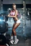 A menina loura 'sexy' da aptidão ajusta o peso no barbell no gym Imagens de Stock