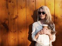 A menina loura 'sexy' nova com cabelo longo nos óculos de sol que guardam uma xícara de café tem o divertimento que nivela a luz  Imagens de Stock