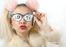 Menina loura vívida e engraçada com as fitas com a inscrição nos vidros 2017 Imagem de Stock