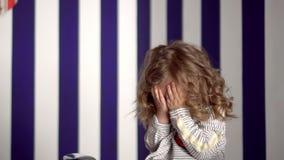 A menina louro custa em um fundo azul A menina bonita com cachos sorri na frente da câmera filme