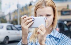 a menina Louro-de cabelo, toma imagens no smartphone, guardando o foto de stock