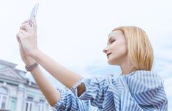 a menina Louro-de cabelo, toma imagens no smartphone, guardando o com ambas as mãos, dia, exterior imagens de stock royalty free