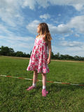 A menina, louro olha no céu azul nebuloso, em torno de seu campo esverdeia Imagem de Stock