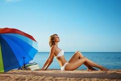 A menina luxuosa encontra-se na praia Foto de Stock