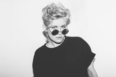 Menina má loura 'sexy' da forma à moda em um t-shirt preto e em óculos de sol da rocha Mulher emocional rochosa perigosa branco Imagens de Stock Royalty Free