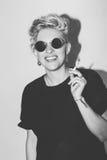 Menina má loura 'sexy' da forma à moda em um t-shirt preto e em óculos de sol da rocha Mulher emocional rochosa perigosa branco Imagens de Stock