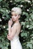 Menina macia 'sexy' bonita com corte de cabelo curto no vestido de creme com flor do jasmim Fotografia de Stock