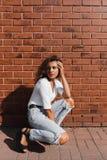 Menina magnífica nova com cabelo encaracolado luz-marrom nas calças brancas do t-shirt e da sarja de Nimes fotos de stock