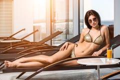 Menina magro atrativa nova no biquini que relaxa na cadeira de plataforma no recurso do hotel dos termas do bem-estar fotografia de stock