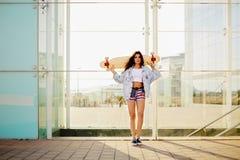 Menina magro bonita no short curto que está com um longboard em sua mão foto de stock