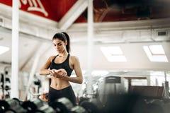 A menina magro bonita vestida no sportswear preto está estando no gym e está olhando seu relógio imagens de stock