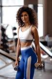 A menina magro com o cabelo encaracolado escuro vestido em um sportswear está fazendo exercícios com pesos no gym moderno com g imagem de stock royalty free