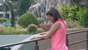 A menina magro com smartphone guarda no corrimão no hotel exótico filme