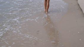 Menina magro do adolescente no vestido branco que anda na praia vídeos de arquivo