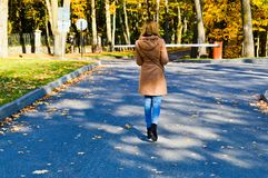 Menina magro fina bonita nova, uma mulher em um revestimento marrom com caminhadas longas do cabelo no parque do outono com folha fotografia de stock