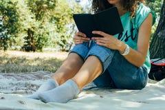 Menina magro nas calças de brim e um t-shirt que leem um livro em um sittin do parque imagem de stock royalty free