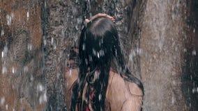 A menina magro no roupa de banho vermelho brilhante toca no cabelo escuro longo video estoque