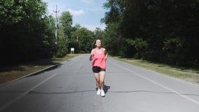 A menina magro nova na camisa cor-de-rosa com fones de ouvido está começando correr no parque Mulher atrativa moreno com o corpo  video estoque