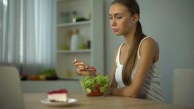 Menina magro que come a salada mas o bolo da ânsia, tendência da forma ser delgado, dieta vídeos de arquivo