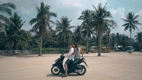 A menina magro senta-se no noivo o par da motocicleta que monta afastado filme