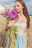 Menina magro 'sexy' bonita em um vestido azul no campo com um ramalhete das flores e das orelhas de milho em suas mãos no por do  Fotos de Stock