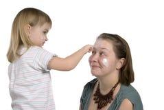 a menina mancha o mum com um creme Foto de Stock
