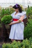 A menina mantém o potenciômetro com a planta no jardim Fotografia de Stock