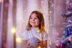 A menina mantém uma bola do Natal disponivel Imagens de Stock Royalty Free