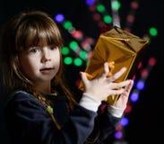 A menina mantém uma caixa com um presente disponivel imagens de stock royalty free