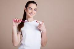 A menina mantém uma escova de dentes e sorri Imagens de Stock Royalty Free