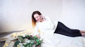 A menina maravilhosa está conversando com o amante no telefone na véspera dos feriados e encontra-se no assoalho da manta ao lado filme