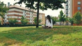 menina marrom moreno bonita do cabelo de 4 k na blusa branca, no short amarelo e nos óculos de sol, sentando-se na grama verde no filme