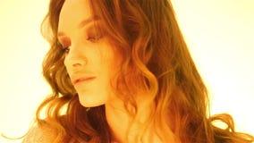 Menina marrom nova do cabelo no levantamento morno das luzes amarelas filme