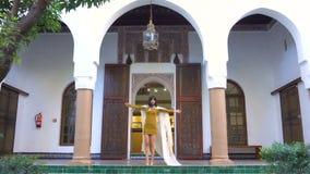 Menina marroquina bonita que acena seu envoltório branco em Dar Si Said Riyad pitoresco em C4marraquexe no tempo do por do sol filme