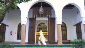 Menina marroquina bonita que acena seu envoltório branco em Dar Si Said Riyad pitoresco em C4marraquexe no tempo do por do sol video estoque