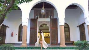 Menina marroquina bonita que acena seu envoltório branco em Dar Si Said Riyad pitoresco em C4marraquexe no tempo do por do sol vídeos de arquivo